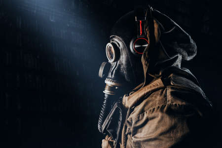 Photo of a stalker soldier in soviet rubber gas mask with  hose, wearing headphones and standing profile view on dark underground backdrop.