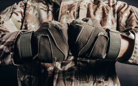 Photo of soldier in camouflaged uniform showing fist fight gesture in tactical gloves on black background.