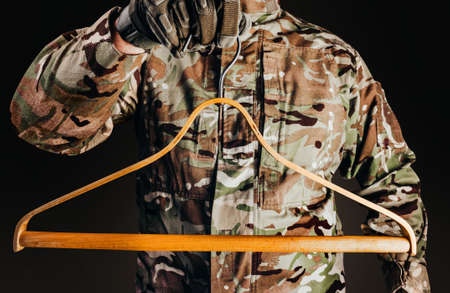 Photo of soldier in camouflaged uniform and tactical gloves holding wooden shirt hanger on black background. Stockfoto