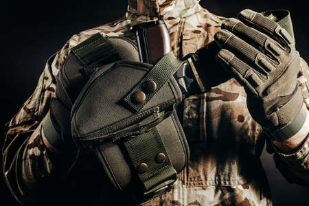 Photo of soldier in camouflaged uniform and tactical gloves holding gun holster on black background. Stockfoto