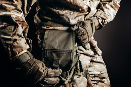 Photo of soldier in camouflaged uniform and tactical gloves using leg bag on black background.
