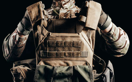 Photo of soldier in camouflaged uniform and tactical gloves holding military armored vest on black background.