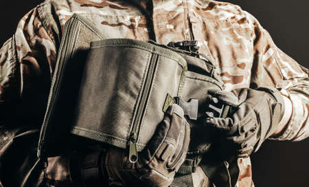 Photo of soldier in camouflaged uniform and tactical gloves holding leg bag on black background. Stockfoto