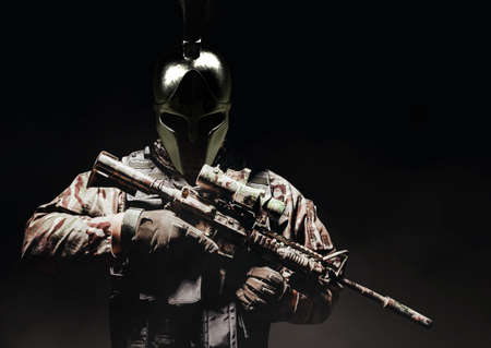 Soldier in armored vest and ammunition standing on balck background in ancient spartan helmet with automatic rifle. Stockfoto