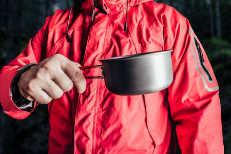 Close-up product photo of hiker man in red travel camping jacket holding metal cup.