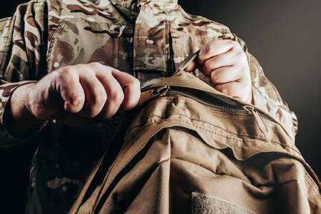Photo of soldier in camouflaged uniform holding and unzipping backpack on black background.