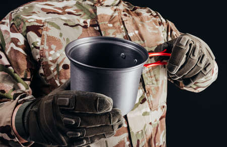Photo of soldier in camouflaged uniform and tactical gloves holding metal hiking dish cup on black background. Stockfoto