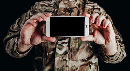Photo of soldier in camouflaged uniform holding smartphone on black background. Stockfoto
