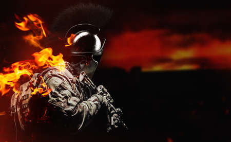 Photo of soldier in camouflaged uniform and tactical gloves holding assault rifle in spartan helmet, profile view.