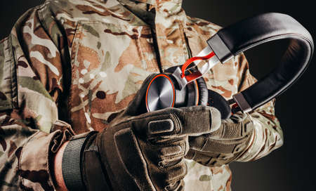 Photo of soldier in camouflaged uniform and tactical gloves holding wireless headphones on black background. Stockfoto