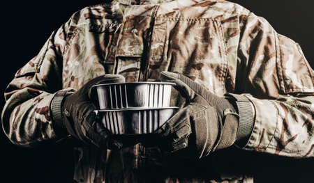 Photo of soldier in camouflaged uniform and tactical gloves holding canned food MRE on black background, close-up view.
