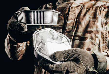 Photo of soldier in camouflaged uniform and tactical gloves holding canned food field ration on black background. Stockfoto