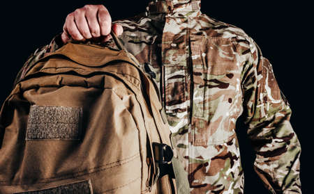 Photo of soldier in camouflaged uniform and tactical gloves holding olive colored backpack on black background. Stockfoto