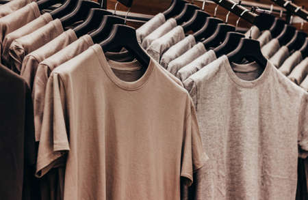 Close-up photo of olive colored soldier tactical t-shirts hanging on stand rack. Stockfoto