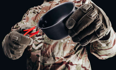 Photo of soldier in camouflaged uniform and tactical gloves holding metal hiking cup on black background.