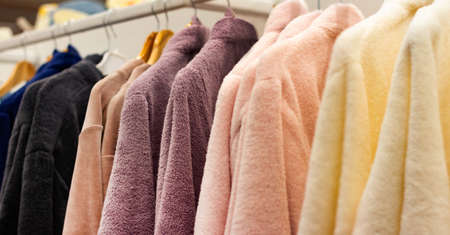 Photo of different colored bathrobes hanging on shopping rack.
