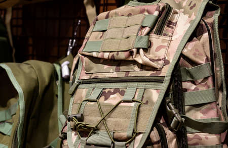 Close-up photo of camouflaged soldier backpack hanging on store stand.