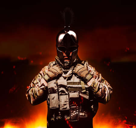 Soldier in armored vest and ammunition standing on burning land background in ancient spartan helmet. Stockfoto