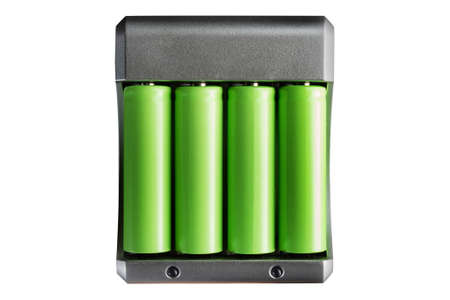 Isolated photo of green colored lithium accumulator batteries in charger on white background. Stockfoto - 164354081