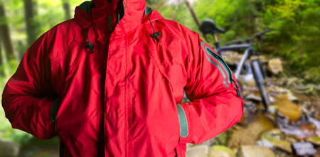 Photo of a male person standing in red travel hiking jacket in summer woods background.