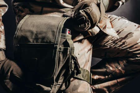 Photo of sitting soldier in camouflaged uniform and tactical gloves using leg bag on black background.