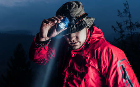 Photo of a male hiker in red jacket and panama putting on head mount flashlight on dark mountain forest background.