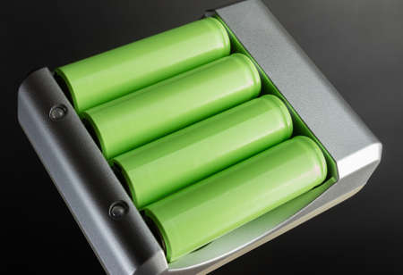 Photo of green colored lithium accumulator batteries in charger on black background.