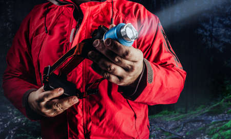Photo of hiker man in red travel camping jacket holding shining head flashlight.