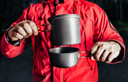 Close-up product photo of hiker man in red travel camping jacket holding metal dishes.