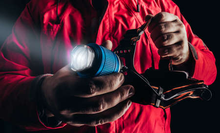 Close-up product photo of hiker man in red travel camping jacket holding shining head flashlight.
