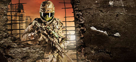 fully equipped soldier in heavy level 3 armor ammunition standing on red destructed city battlefield background with destructed walls copyspace backdrop. Stock fotó