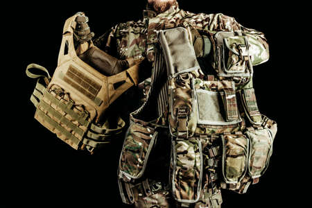 soldier holding various types of camouflaged armored vests on black background. Foto de archivo