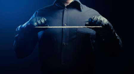 Photo of a shaded strangler assassin man in black shirt and leather gloves holding rope.