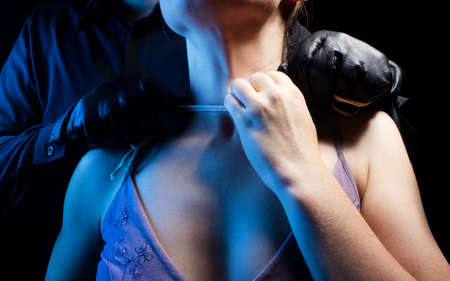 Photo of assassin killer man in black shirt and leather gloves strangling woman on black background.