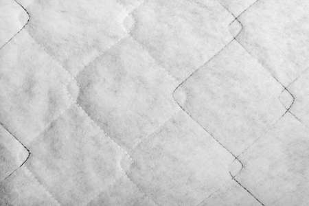Texture backdrop photo of white colored sintepon fibers material with stitching pattern.