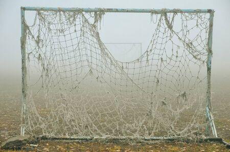Altes leeres verlassenes Fußballfeld und Tor mit einem wirren Netz im Nebel