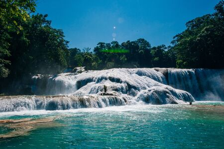 Agua Azul, Chiapas, Palenque, Mexico. View of the amazing waterfall with turquoise pool surrounded by green trees.