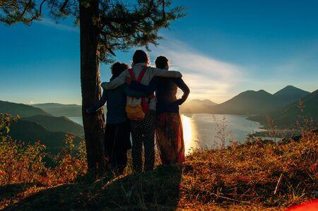 Rückansicht einer Gruppe von Freunden, die zusammen auf einem Berg stehen und die Morgendämmerung auf dem Atitlan-See betrachten