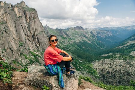 Woman sitting on mountain with beautiful nature background in russia