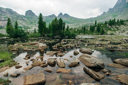 Mountain lake, Ergaki National Park. Crystal clear water, rocky mountains and clear sky.