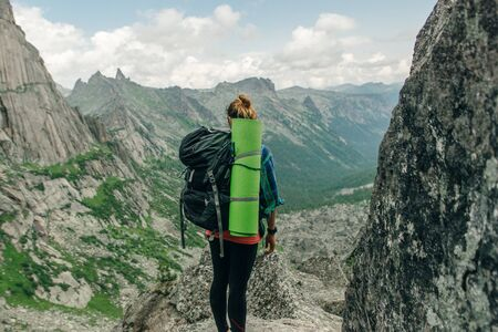 Hiking in mountains. Woman Traveler with Backpack hiking in Ergaki