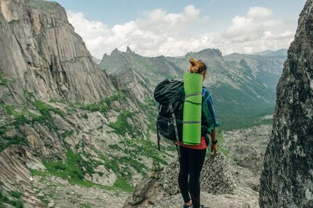 Hiking in mountains. Woman Traveler with Backpack hiking in Russia