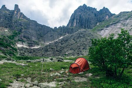 Camping with a red tent in the mountains in Russia, ergaki