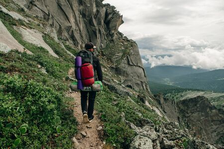 Tourist with a backpack in mountains panorama Stok Fotoğraf