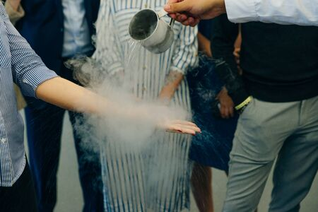 Chemical event at the birthday party: childrens hands touch the smoke from liquid nitrogen. The view from the top. Reklamní fotografie