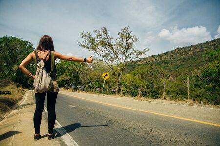 Cute latin American woman hitchhiking