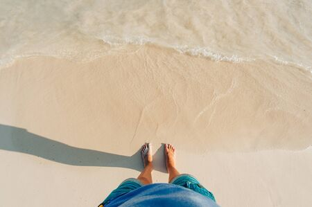 above view of sandy beach with waves and clear ocean water. Stock Photo