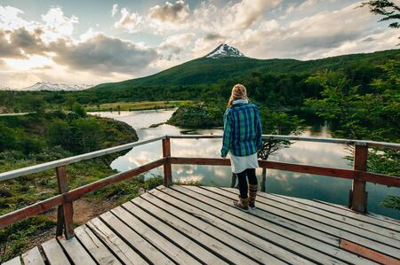 Woman walking in a balcony with a beautiful landscape in the background. Ushuaia