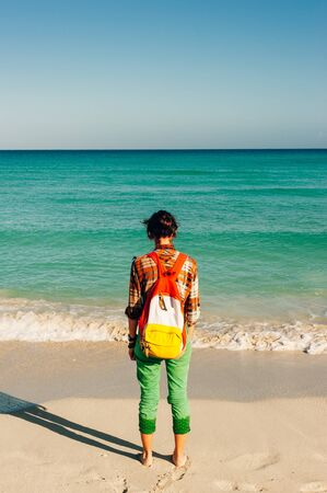 Brunette woman traveler standing on the beach with a backpack. varadero