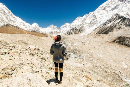 Paesaggio con ragazza, alte montagne con cime innevate, sentiero, cielo blu in Nepal. Viaggio. Archivio Fotografico